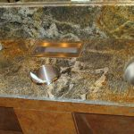 granite bathroom counter with built in trash and kleenex dispenser