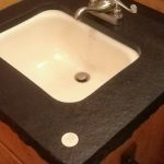 Inlaid 100 year old silver dollar into absolute black granite bathroom counter
