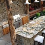 Outdoor granite kitchen with hand scribing around log beams