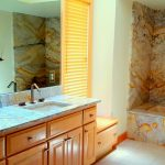 Full granite slab tub walls, tub deck and surround, matching granite counters with undermount sinks