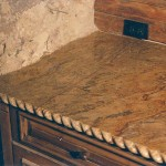 Hand carved granite rope edge along entire counter, hand scribed granite along stone wall